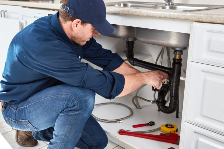 Plumber Fixing The Kitchen Sink - plumbing services in Chicago, IL